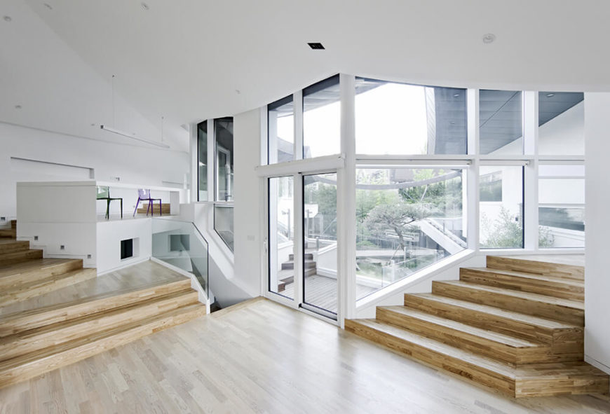 From the main living room, we can see the sprawling, multi-layered courtyard through full height windows. The contrast between sharp modern forms and natural environment is a centerpiece of the home's design.