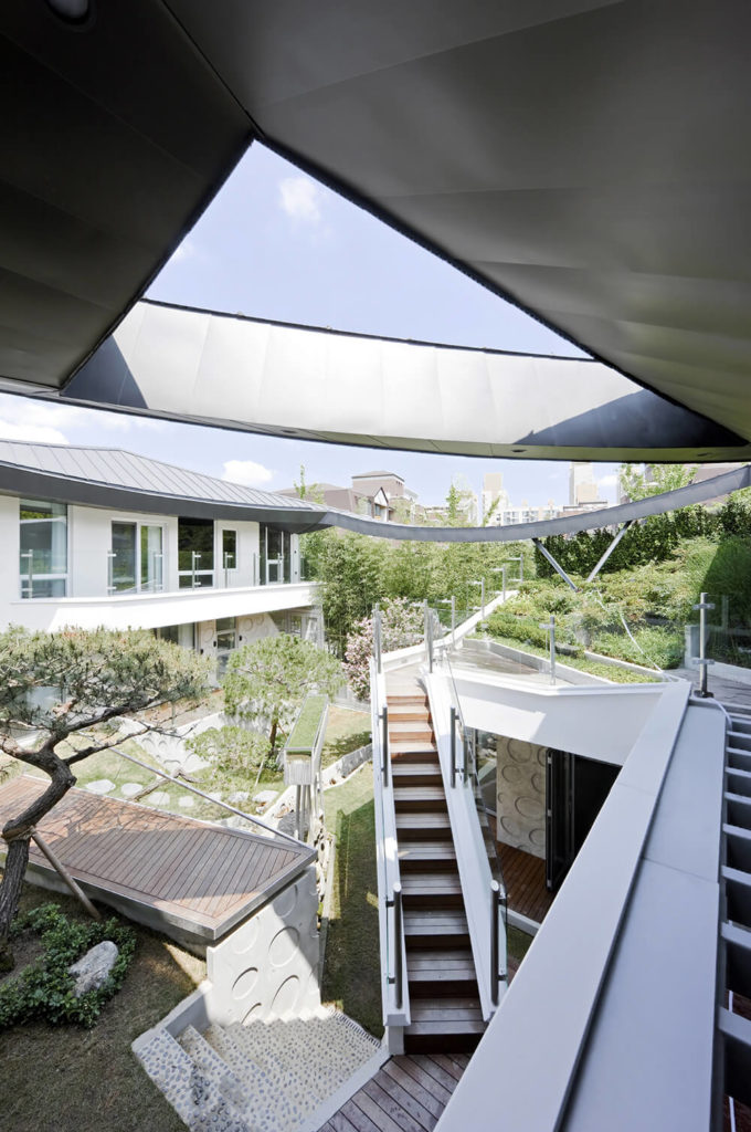 From just below the roof, we can see the way the densely planted sets of trees and grass blend with the architecture for a truly adventurous experience.
