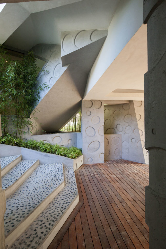 Now we return to the lower entrance space for another look at the traditionally styled concrete walls and rich wood flooring. Stones embedded in the entry steps emphasize this latent connection to nature.