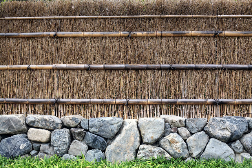 This is a beautiful, rustic example of a bamboo and reed fence. Thicker stalks of bamboo form horizontal support bands, while the interior is packed with dense reed bamboo to create a thick barrier.