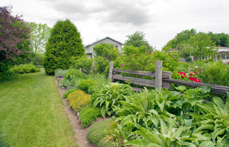 A Rustic Split Rail Fence Used To Separate Different Sections Of Large Planting Bed