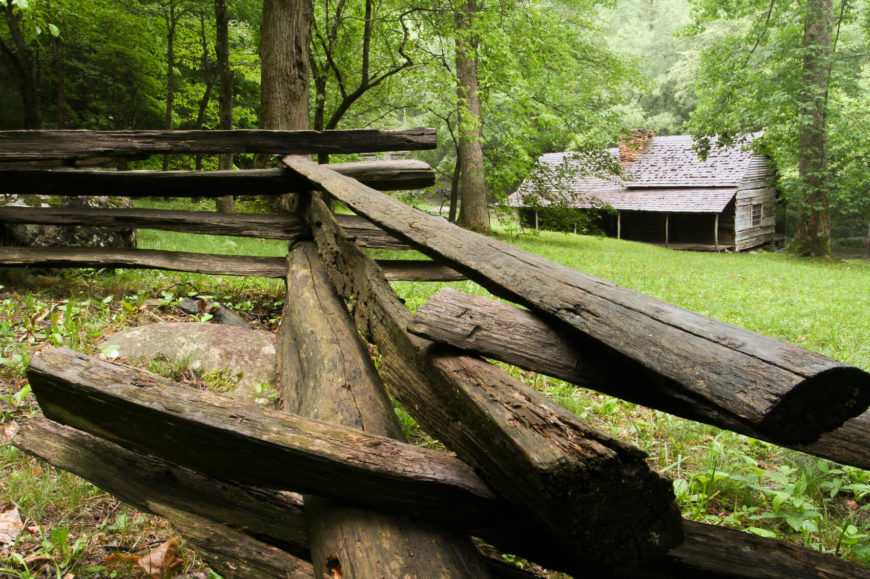 An aged rustic traditional split rail fence marking the boundary of this cabin on a heavily wooded lot. The tin roof of the cabin gives it a decidedly rustic look.