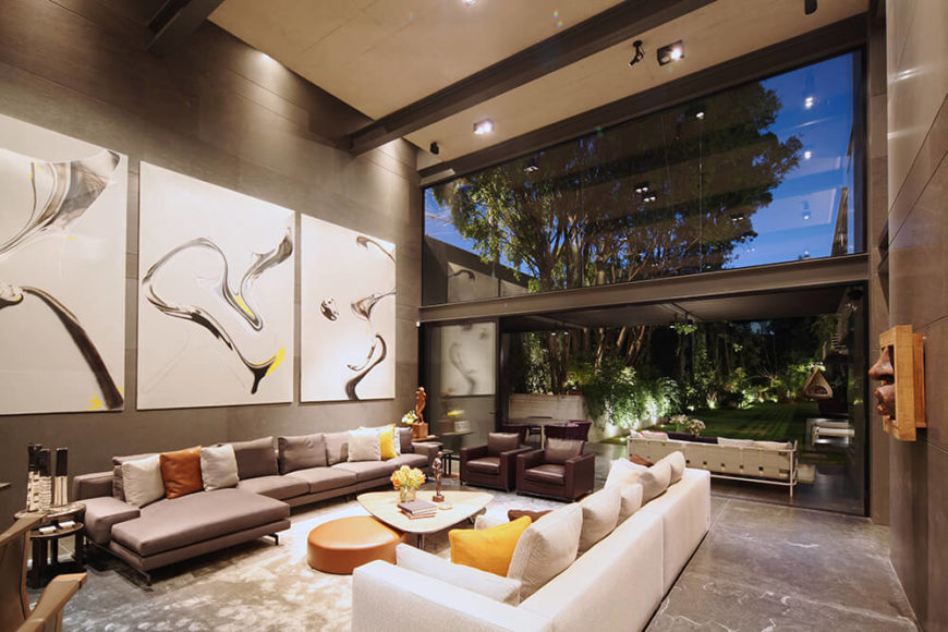 Turning the other way, we see through the completely opened glass panels to the patio, noting how the open design blurs the line between indoors and out. Artwork placed throughout the home lends a sense of personality and character to the open plan design.