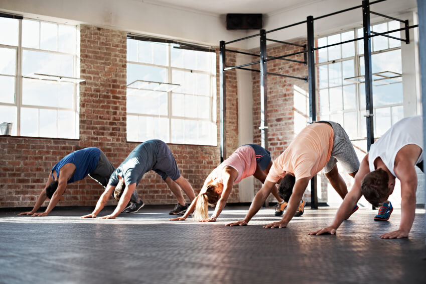 Yoga studio with brick walls, large windows and dark floor.