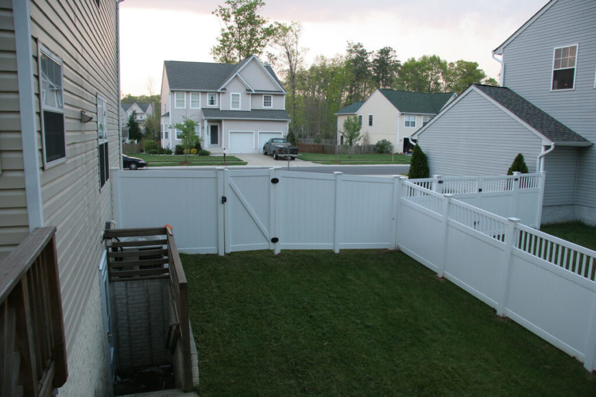 A Residential Vinyl Fence With A Gate Leading To The Front Yard. The Side Of