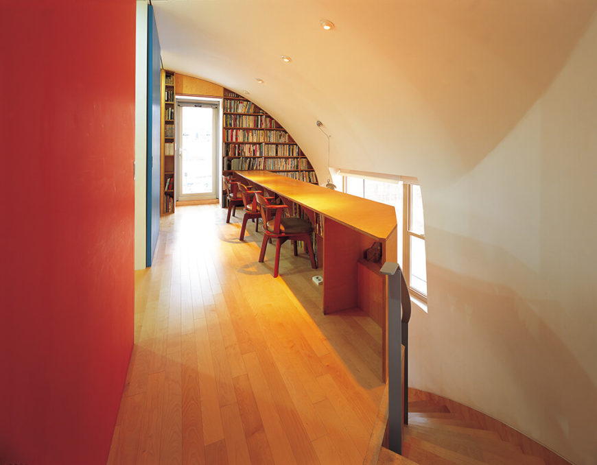 Moving inside the home, we see how the organic curves of the exterior play out inside. The sharp angled brick gives way to smooth white walls and rich natural wood, highlighted by splashes of primary color.