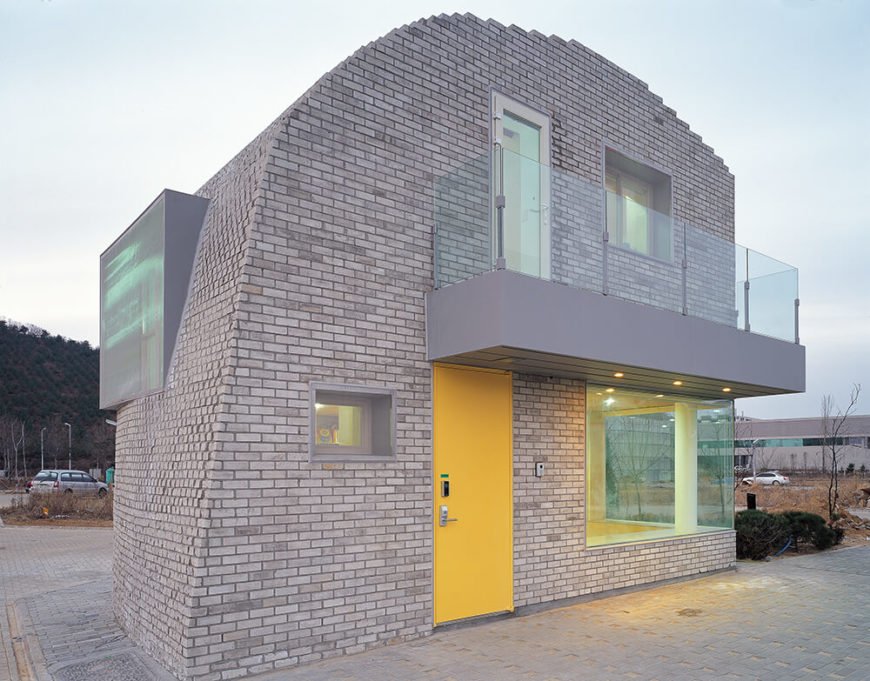 Here's a close look at the visually striking home, its organic curves turned staccato at the edges where we see individual bricks exposed. The large windows and bold yellow door make for a complex appearance.