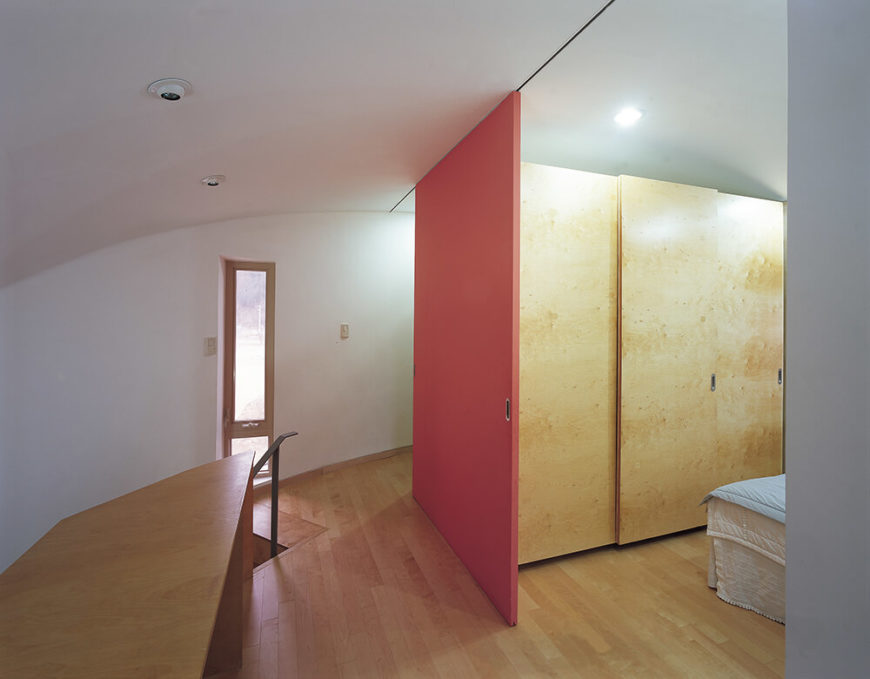 Moving back upstairs, we come to the private areas of the home, including this bedroom at right. Using simple but brightly colored sliding panels to enclose and reveal discrete rooms, the open plan becomes dynamic and accessible.