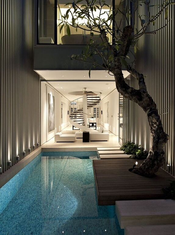 Another beautiful indoor pool just off the living room. It functions dually as a hallway, with stone stepping stones leading along the side of the pool. A large tree adds an element of organic beauty.