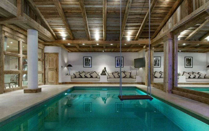 A spacious and rustic-contemporary indoor pool with a mirrored wall along the right side and twin sofas along the back wall. A simple rope swing hangs above the water from the vaulted wooden ceiling.