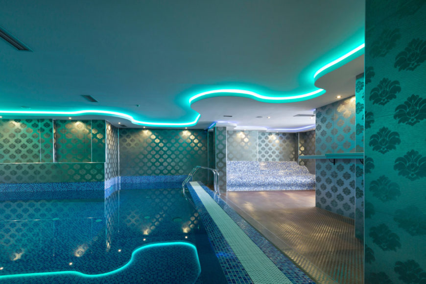 Another indoor pool area with unique, metallic wallpaper throughout. The ceiling is lighted with an aqua rope lighting that compliments the tile work and wallpaper.