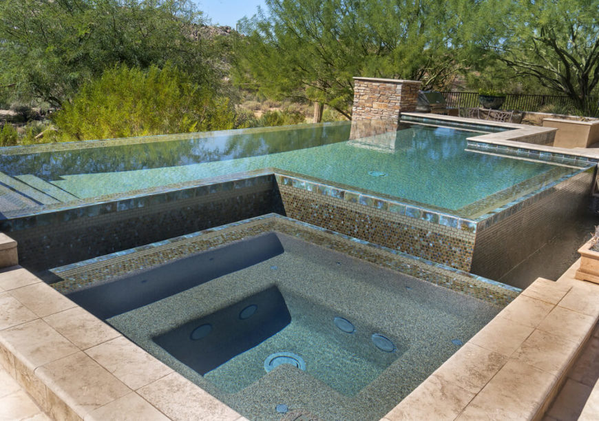 This is a unique pool complex featuring an infinity pool with a moat surrounding it to catch any water sloshing over the edge. On the other side of the moat is a sizable hot tub.