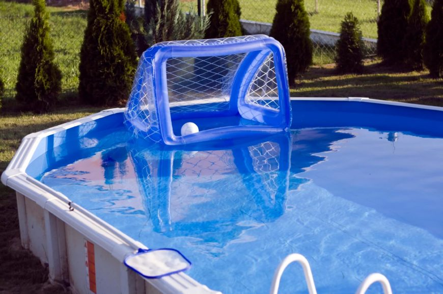 A simple above ground swimming pool in white with a pool ladder and an inflatable water polo goal set up on one side.