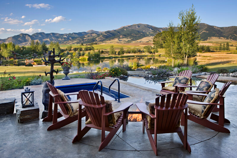 This patio looks out over the countryside, which includes a mountain range and a large pond. Near the fire pit is a regular infinity pool along with a plunge pool.