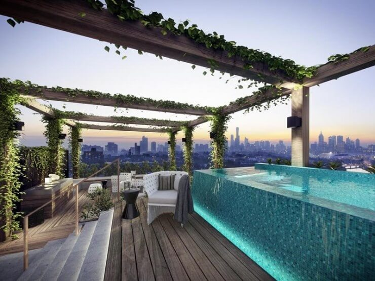 This beautiful glass pool is transparent, so that only the aquamarine tiles on one side can be seen. Pergolas covered in thick vines are placed above the pool and the surrounding patio.