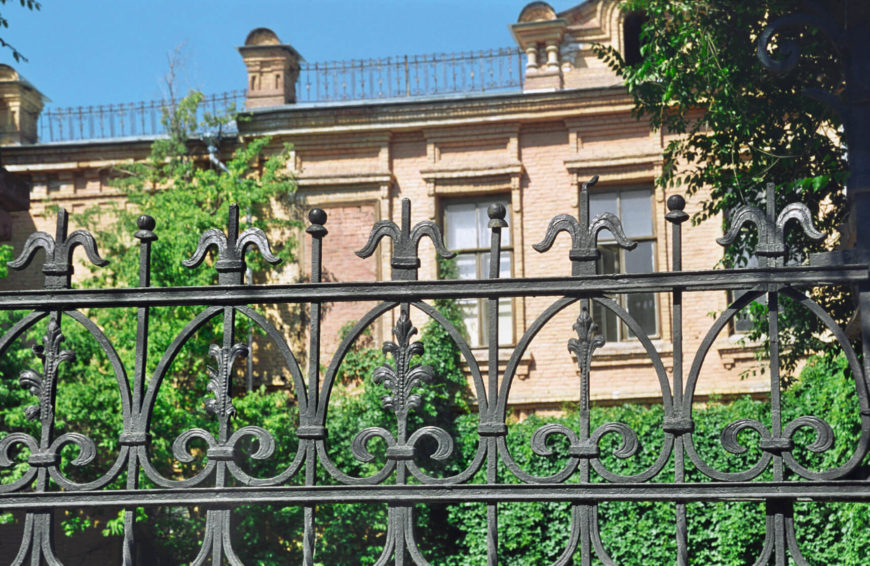 Classic Wrought Iron Fence In Front Of A Hedge Garden