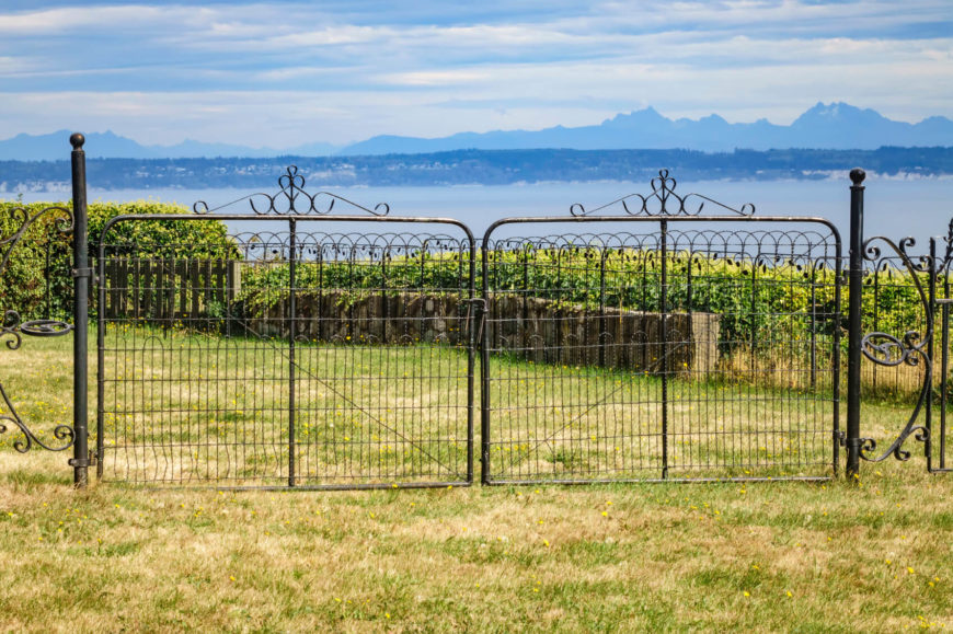 Beautiful wrought iron gate over looking a vineyard on a hillside. This fence is more decorative than anything else.