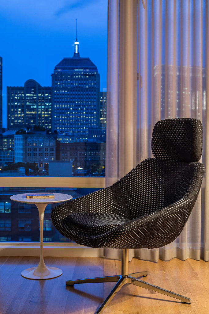 Here's another example of the thoughtful and unique furniture choices that help define the look of this home. Standing in a nook near the kitchen, this elegant reading chair and minimalist table stand with expansive views over Boston.