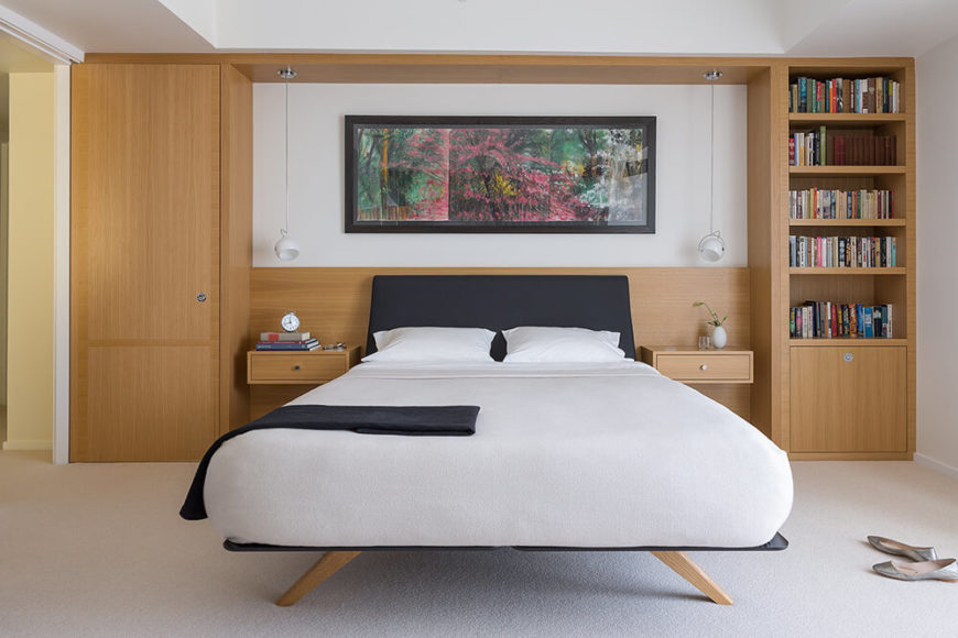 The bedroom continues the blend of rich wood tones and modern minimalist styling, with a wall-size shelving and storage unit backing the sleek and contemporary bed. A single colorful work of art hangs on the wall in lieu of a headboard.