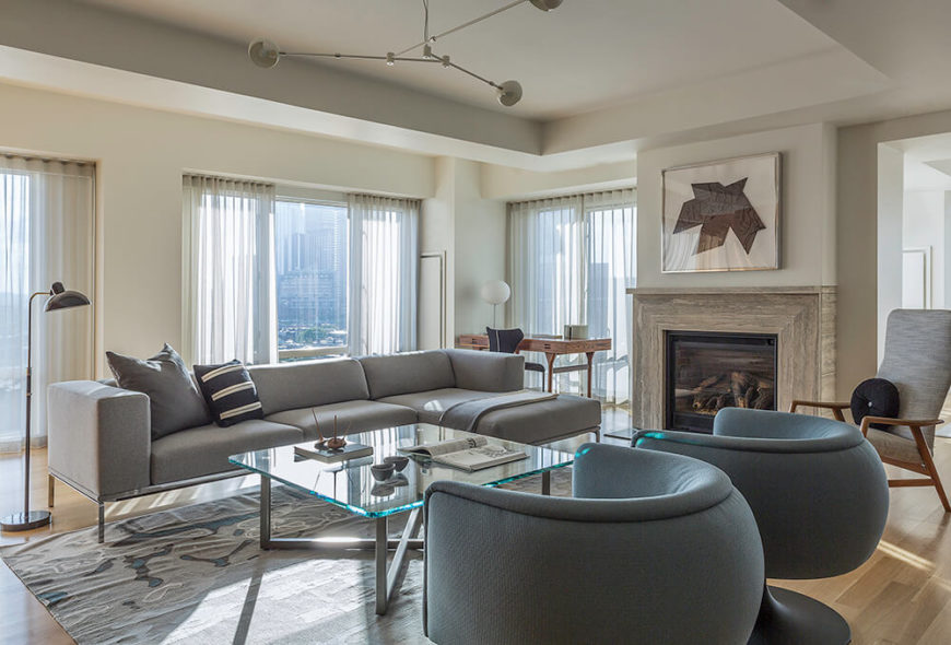 The living room centers on a sleek set of furniture, including a pair of spherical club chairs and a contemporary grey sectional sofa, plus a steel and glass coffee table at center. A marble fireplace stands between the doorway and one of several full height windows.