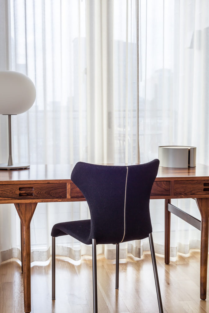 A home office space is populated by this stylish and elegant all-wood writing desk. The slim design and shape mesh with the modern look of the penthouse, while the rich wood construction offers a sense of timeless warmth.