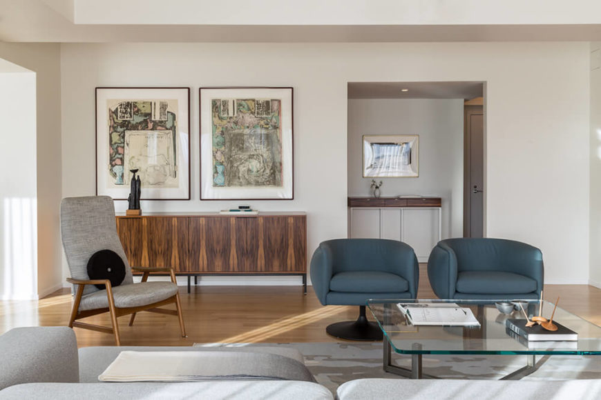 On the opposite wall we see a simple wood hutch below a pair of paintings, and the main entryway to the right. A lone tall-back accent chair bridges the stylistic gap between the warm wood tones and cool, minimalist aesthetic.