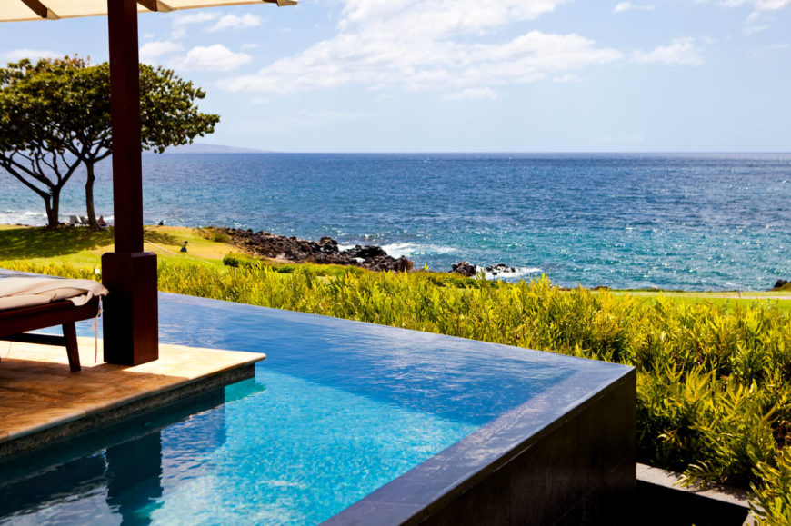 This is a stunning and elegant infinity edge pool that wraps around a deck. This is a clever and interesting method to fit a pool into a smaller space.