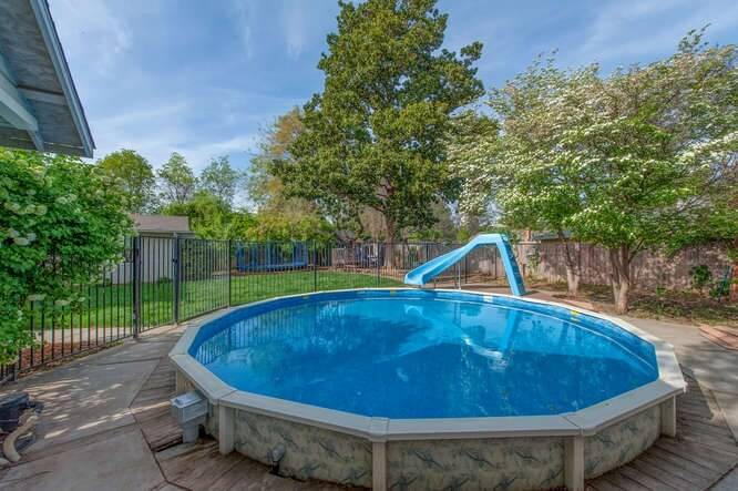 this round above ground pool is surrounded by a concrete pool area and adorned with - Above Ground Pool Deck Off House