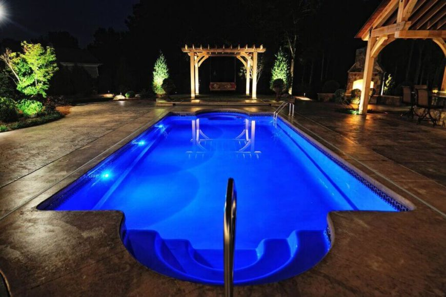 A beautiful Roman style pool with spectacular blue lighting. the lighting illuminates the pool making this pool even more visually appealing at night.