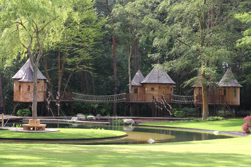 From across the lake, we can see the full set of treehouses connected by wooden bridges. A large Willow with benches surrounding the truck sits in the center of the lake.