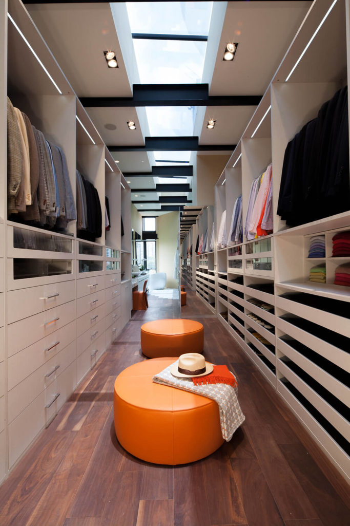 Moving further backward, we see the vast walk-in closet that leads to the master bath, arranged in the same narrow layout. White shelving and rich hardwood flooring are punctuated by a pair of bright orange ottomans.