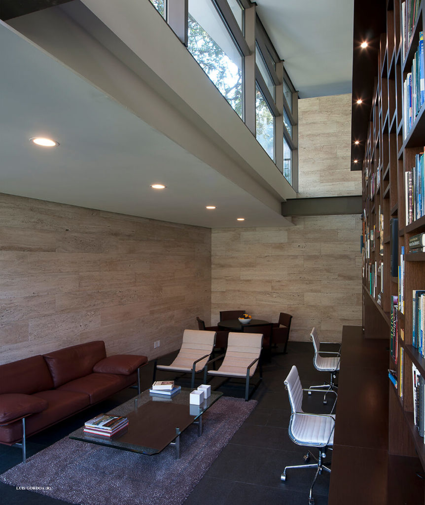Moving back inside, here we see a smaller family room, anchored by stone flooring and rich wood shelving. The sleek modern furniture makes a nice light counterpoint to the heavy building elements.