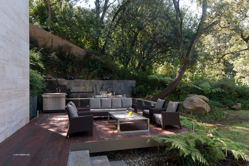 The structure is surrounded by pockets of outdoor comfort, like this small patio backed against the hillside. The stone border fence acts as a visual anchor for the rich wood deck.