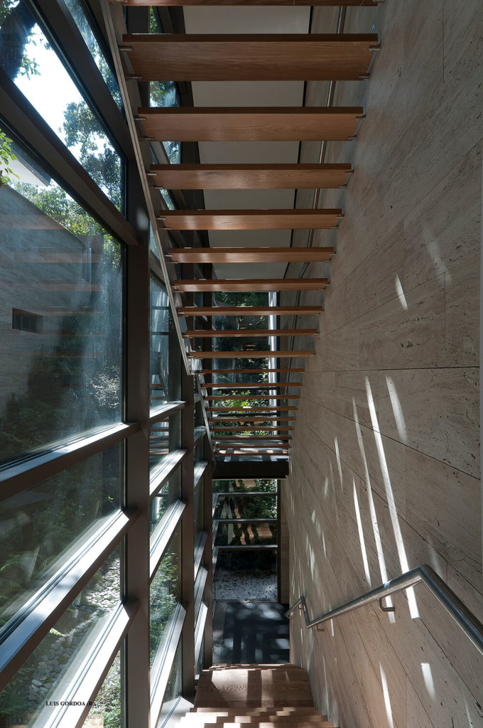 Turning the opposite direction, we see the stairs continue down to the ground level, tucked beneath the actual soil line of the landscape. The open design of the staircase makes for open visual lines and a more expansive interior presence.