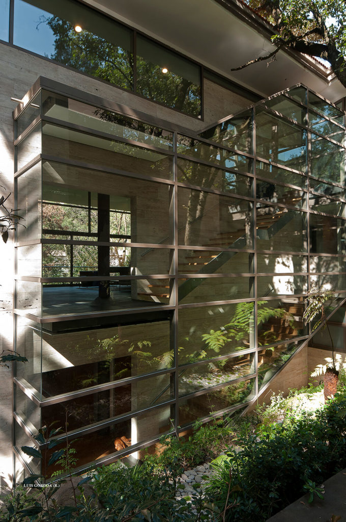 Here we see the massive staircase system from outside, wrapped in glass and crisscrossed by steel beams. The interior structure seems to float independently of the exterior shell.