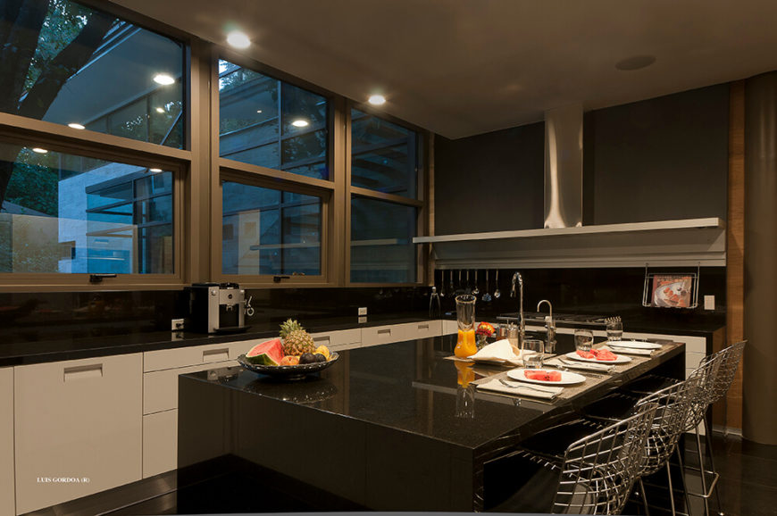 The kitchen is full of sleek, glossy, high contrast materials like the black island and white cabinetry. The natural woods are kept to a minimum here, evoking a more modern look.