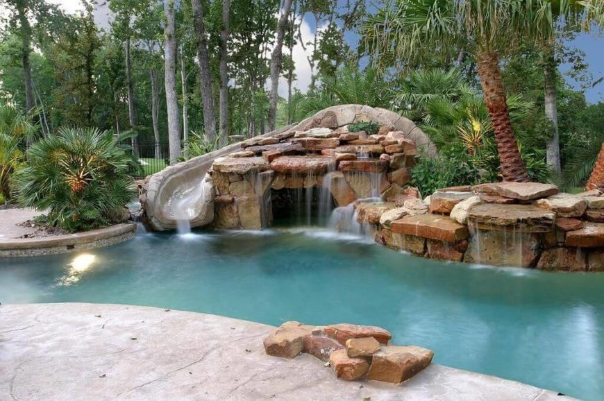 this is a detailed slide with a faux stone design set into some stone and waterfall - Swimming Pools With Waterfalls And Slide