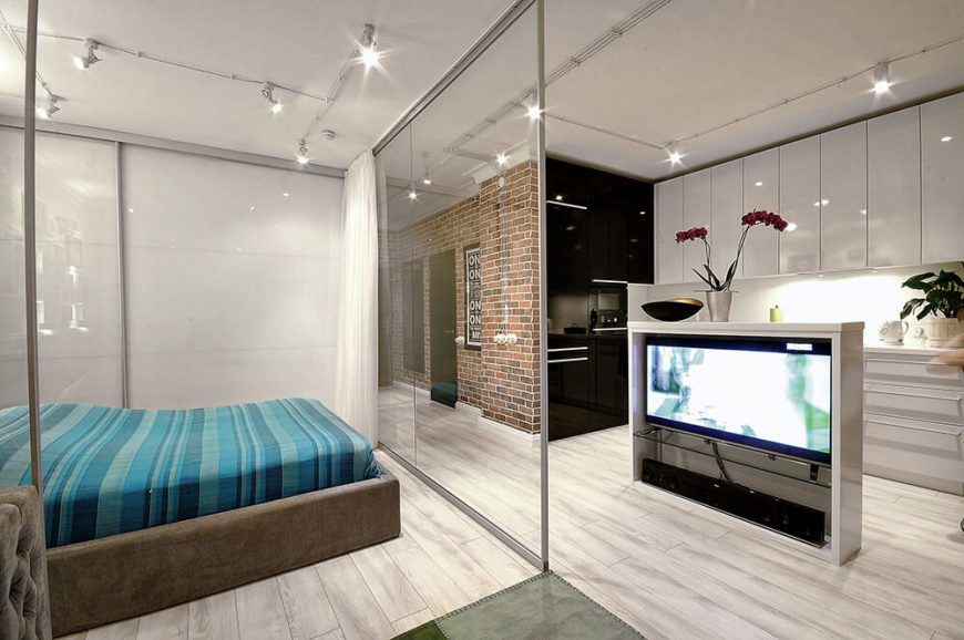 As we take a step back, we see the way the bedroom is enclosed behind glass, which allows it to feel private but still allows access to the television. The cabinet with the television creates a dividing barrier between the kitchen and entertaining areas.