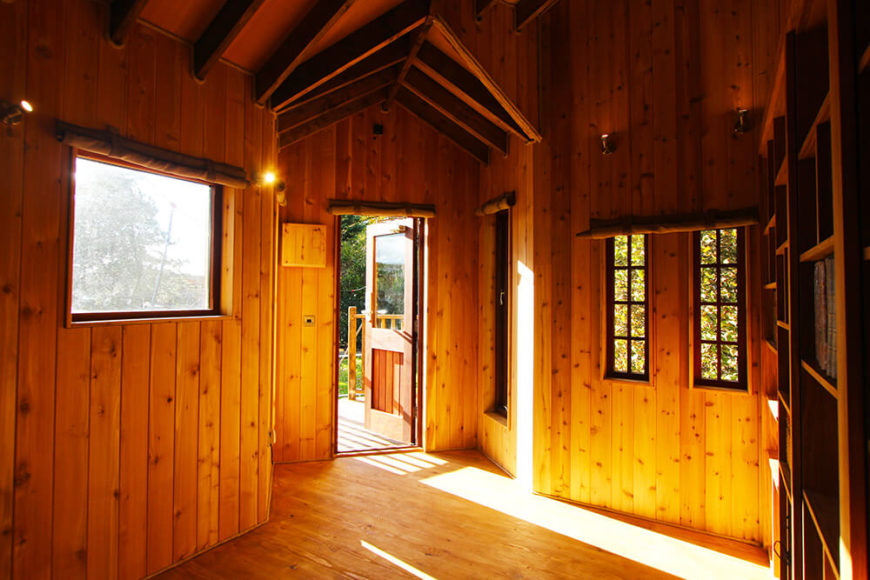 The main entrance opens to a wide open space within the treehouse, below a vaulted ceiling and acres of rich natural wood paneling all around. The diverse windows cast plentiful sunlight in here.