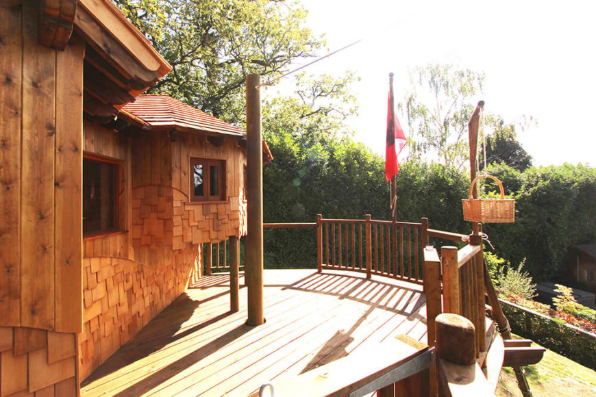 Here we see the expansive deck wrapping the treehouse, all in rich natural wood for a warm, inviting look. The zip wire connects here, as does the lift and load basket mounted to the right.