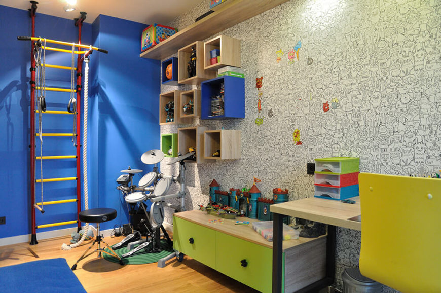 The first of the children's rooms is located next to the office, and has an incredible coloring book wallpapered wall. Bold colors, a drum kit, and exercise equipment ensure that the child has plenty of ways to express himself.