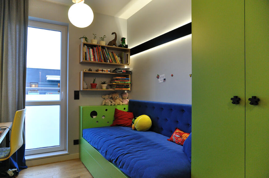The other child's room has the same light fixture and color scheme, but is slowly transitioning to a more adult-like appearance. A desk is on one side of the room.