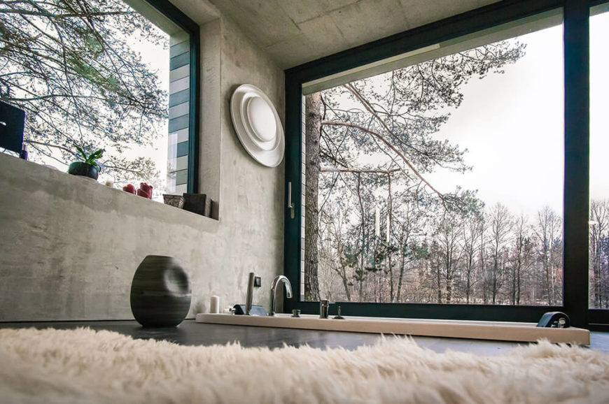Large windows characterize this bathroom, which features an incredible sunken soaking tub. It's easy to imagine relaxing in the bathtub and being able to look out the floor to ceiling windows.