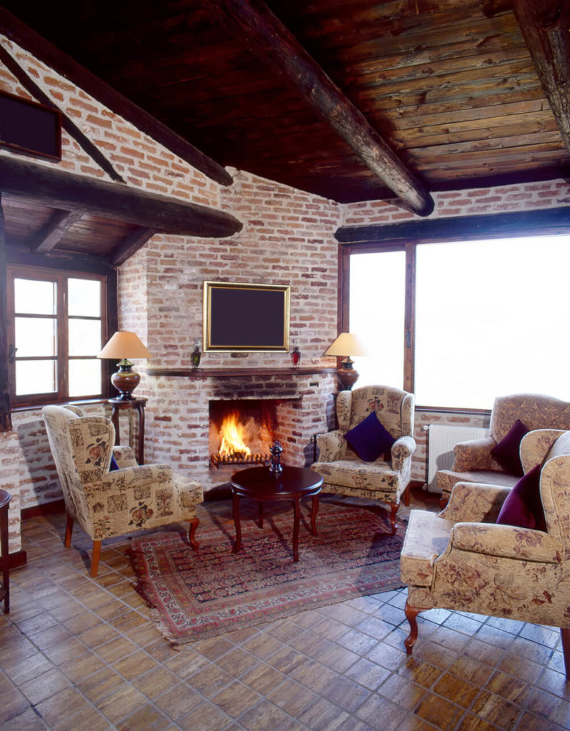 Three Cozy Looking Wingback Chairs Around A Round Table And A Fireplace.  These Chairs Are