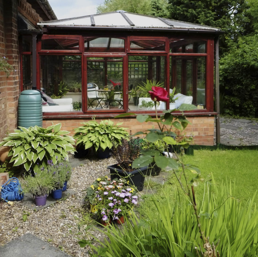 Here is an attached greenhouse with a foundation and glass for its glazing. This greenhouse is large enough to have some seating. It's a perfect year round escape into a lovely verdant garden.