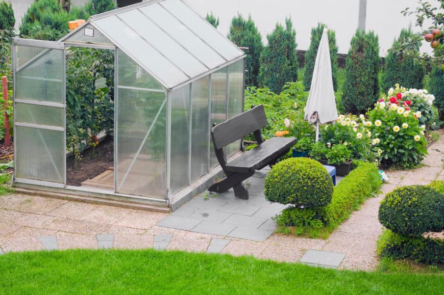 This Simple And Personal Greenhouse Is Surrounded With Nice Landscaping And  A Bench To Relax On