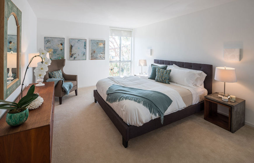 This bedroom is more liberal with the color, using various shades of teals to lighten up the neutral walls and bedding. Paintings replace personal photos, and an orchid adds a bit of organic, tropical beauty.
