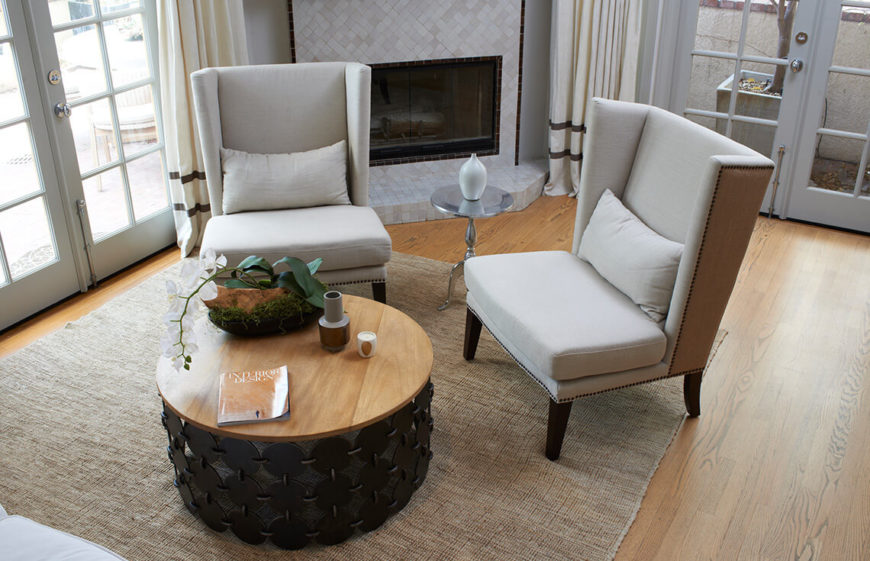 This space uses a simple layout to maximize space and create appeal. This simple and symmetrical layout of the furniture paired with the reserved use of the staging items on the table make a warm and inviting place without being overly busy and cluttered.