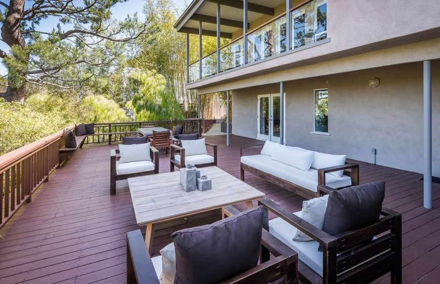 This large and appealing deck is staged with fantastic neutral furnishings in multiple areas. The near area is a perfect gathering area, that can have buyers picturing staging all sorts of functions in their lush backyards.