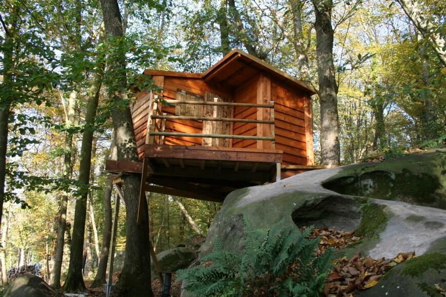 Perchée entre un rocher et un arbre, cette maisonnette donne sur une forêt pleine de mystère.  Nous aimons la riche teinte rouge du revêtement.